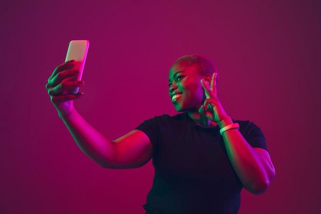 紫ピンクの背景にアフリカ系アメリカ人の若い女性の肖像画