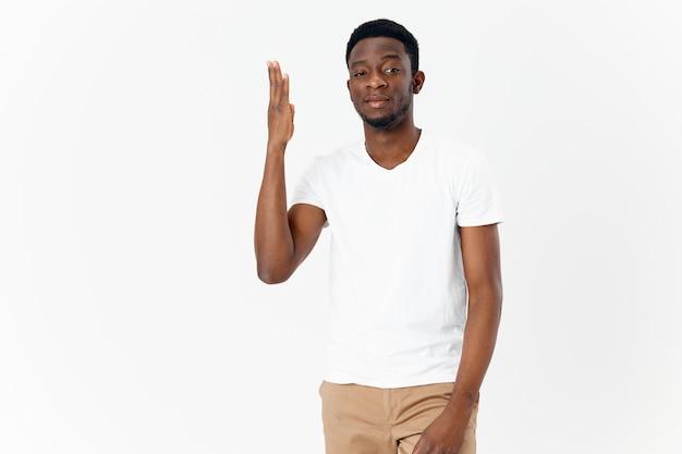 手のライフスタイルで身振りで示すtシャツのアフリカ風の男
