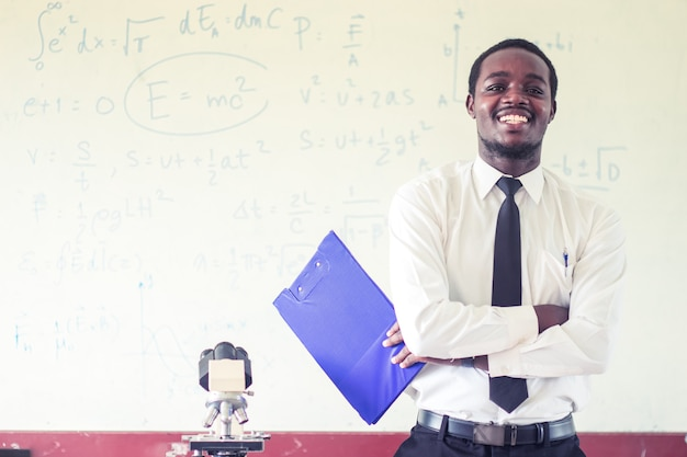 Africanman science teacher smiling in the classroom with microscope.