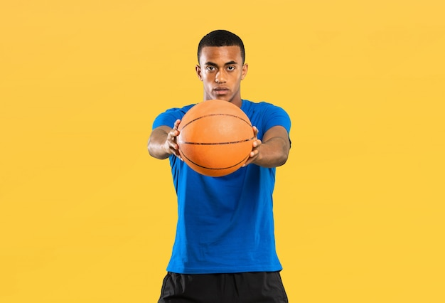 Afro american basketball player man over isolated yellow background