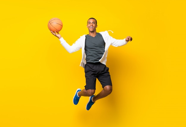 Afro american basketball player man  isolated on yellow