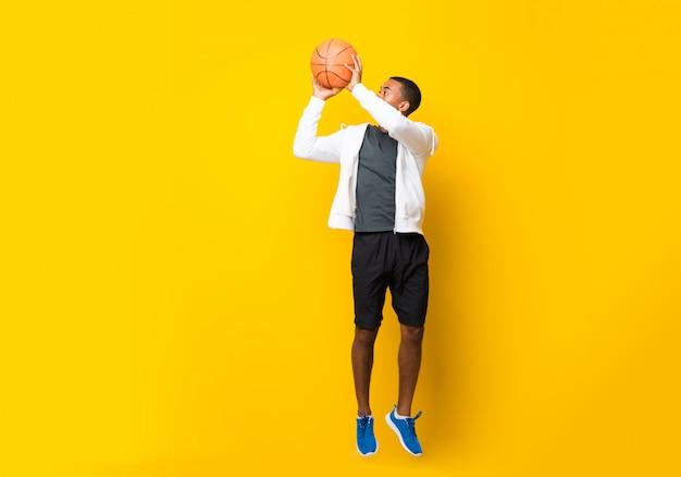 孤立した黄色の背景の上のアフロアメリカンバスケットボールプレーヤー男