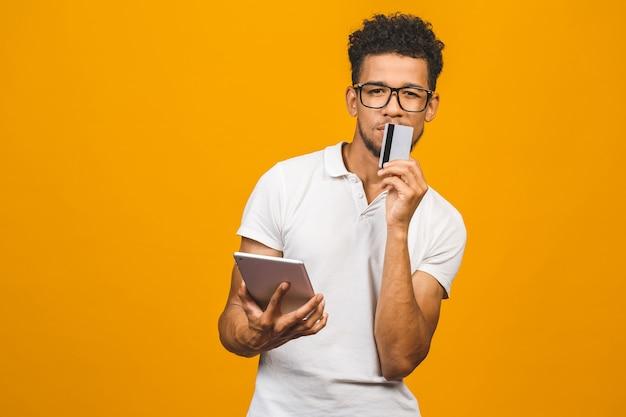 아프리카 미국 흑인 남자 태블릿 pc를 사용하여 온라인 쇼핑 및 신용 카드로 결제