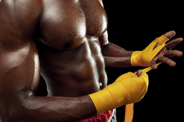 Afro american boxer is wrapping hands with yellow bandage