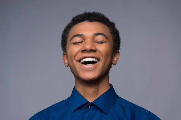Afro american boy with good mood smiles on camera.