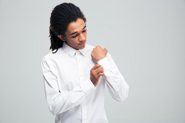Афро-американский бизнесмен, застегивая рубашку над серой стеной