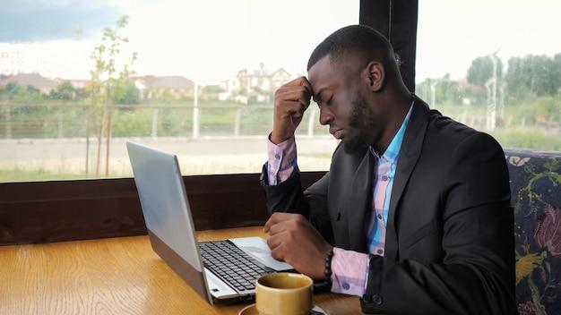 アフリカ系アメリカ人のビジネスマンは、カフェに座っているコンピューターで入力しようとします。黒人男性はラップトップで作業していますが、壊れていて、緊張してキーをノックしています。彼はコンピューターの問題を抱えています。電池残量が少なくなっています。