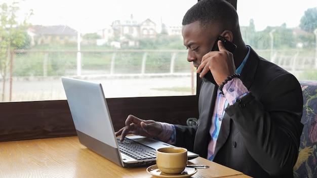 Афро-американский бизнесмен работает на ноутбуке и разговаривает по мобильному телефону в кафе. у него чашка кофе. черный человек звонит на мобильный телефон и ищет документы на компьютере. он носит рубашку и пиджак.