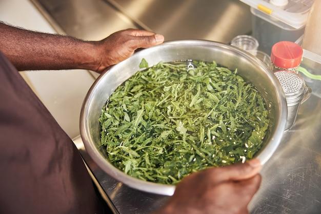 부엌에서 그릇에 녹지를 세척하는 아프리카 미국 밥 솥