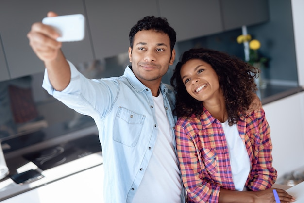 Афро американская пара делает selfie на кухне.