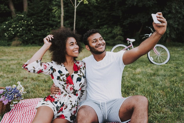 Afro american couple doing selfie in wood