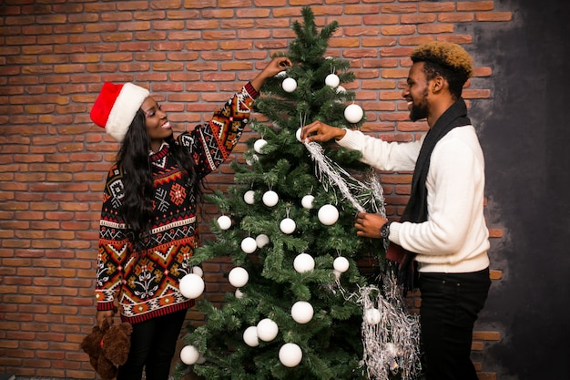 Afro american couple hanging toys on a christmas tree
