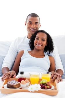 アフロ・アメリカ人のカップルが朝食をベッドに横たわっている