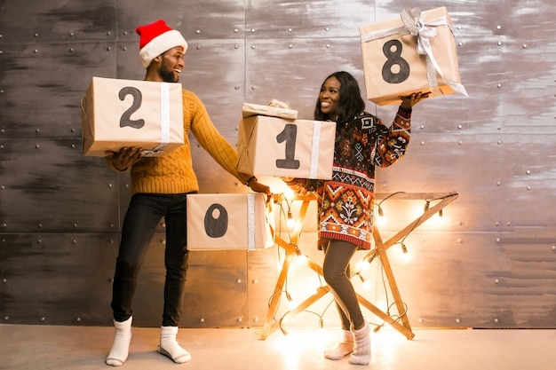 Afro american couple holding christmas presents