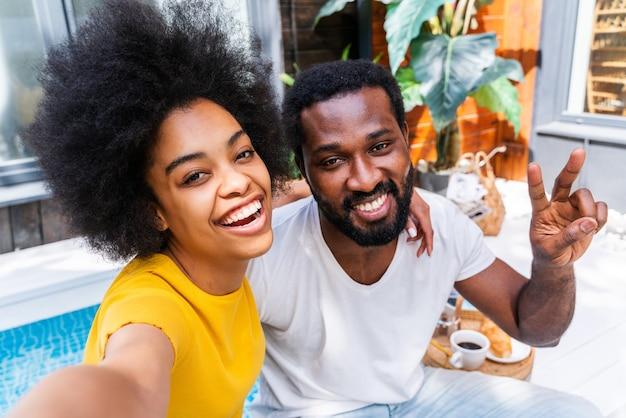 庭で家にいるアフロアメリカ人のカップル-一緒に時間を過ごす美しい黒人のカップル