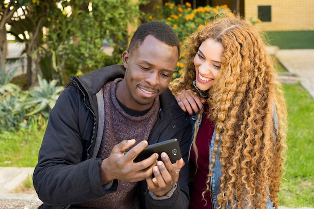 Afro american couple looking at smartphone