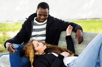 Afro american couple on bench in park