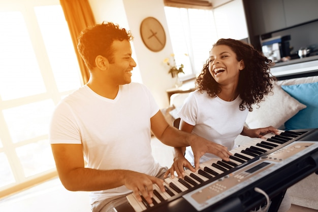 Afro american couple playing on synthesizer