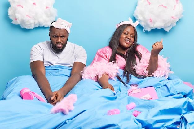아프리카 계 미국인 부부는 담요 아래 편안한 침대에 함께 포즈를 취하고 파란색에 고립 된 수면을 준비합니다.