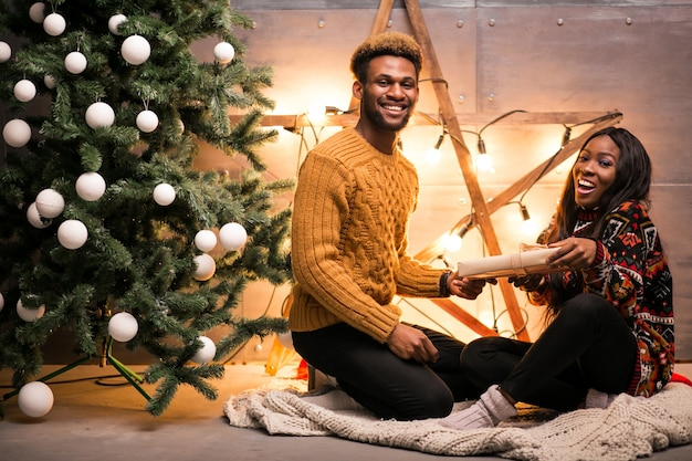 Afro american couple sitting by the christmas tree