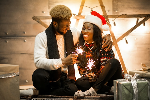 Afro american couple sitting with bengal lights