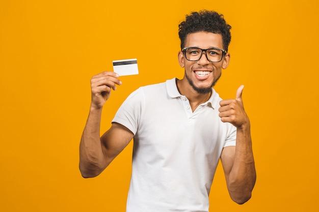 Okの標識をやって笑顔で幸せなクレジットカードを保持しているアフロアメリカンの顧客男