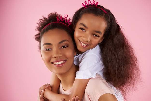 Afro american daughter and mother in sham crowns