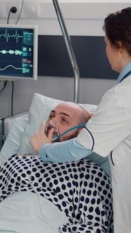 여자 의료진이 호흡 질병을 모니터링하는 산소 마스크를 씌우는 동안 클립 보드에 증상 질병을 쓰는 아픈 남자와 논의 아프리카 미국 의사