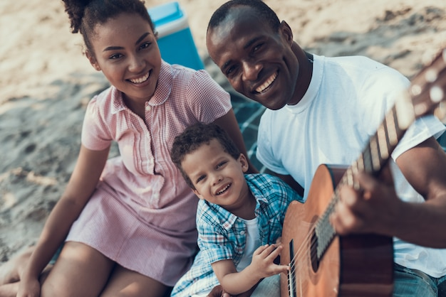 Afro-american family is resting on the beach