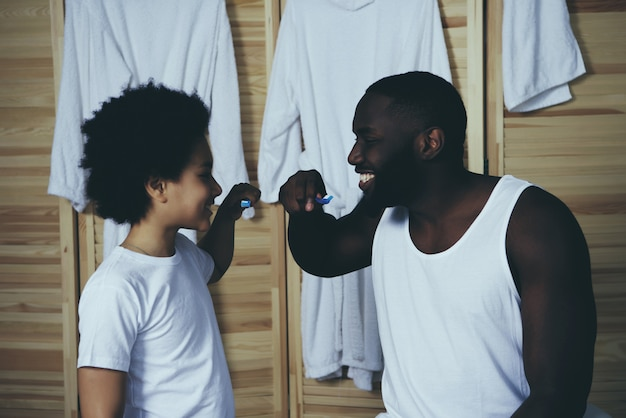 Afro american father and little son brush teeth