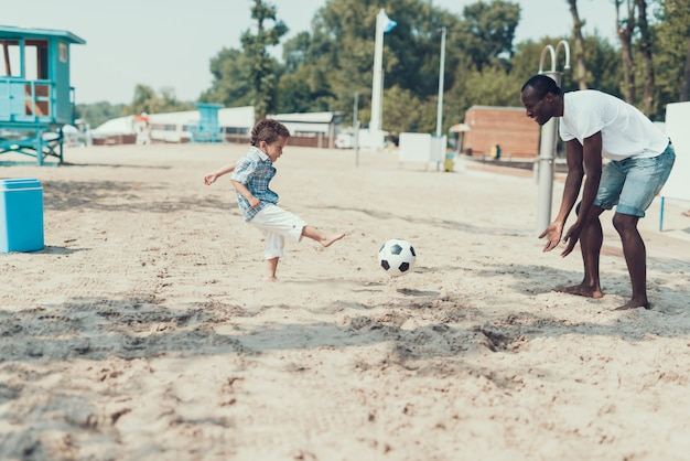 Afro-american father and son are playing with football ball