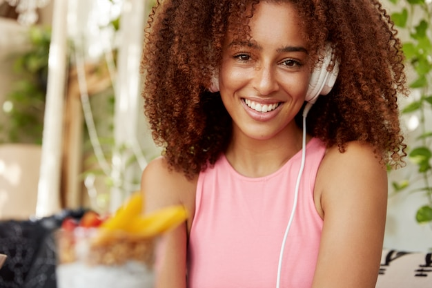 Afro american female student listens songs from playlist, enjoys perfect sound in modern headphones, has cheerful expression, sits against cafe interior. people, leisure, entertainmet concept