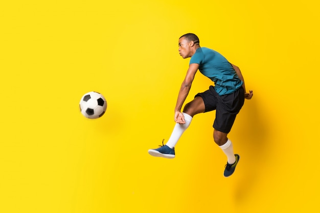 Afro american football player man over isolated yellow wall