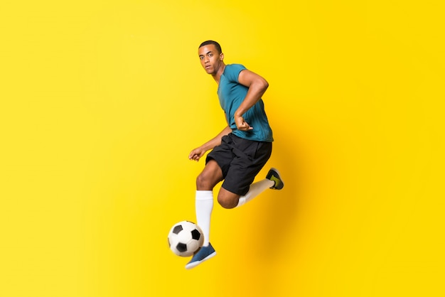 Afro american football player man over isolated yellow