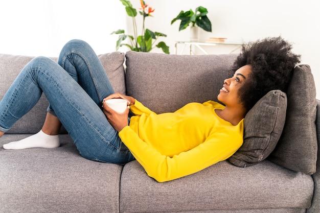 커피 한 잔을 마시고 집에서 휴식을 취하는 아프리카계 미국인 소녀
