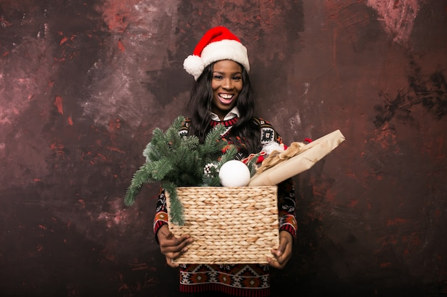 Afro american girl holding christmas decorations in a box