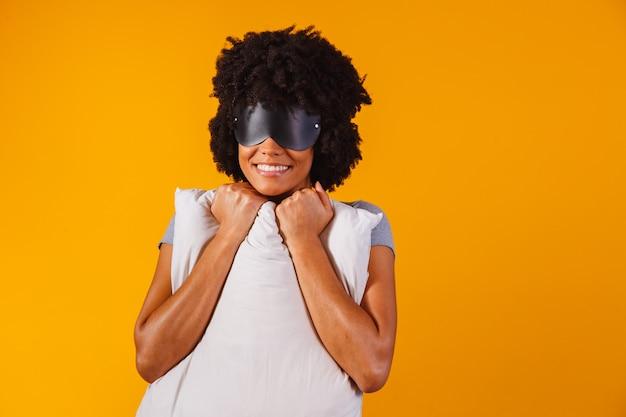 Афро-американская девушка в пижаме и маске для сна обнимает подушку и улыбается на желтом фоне
