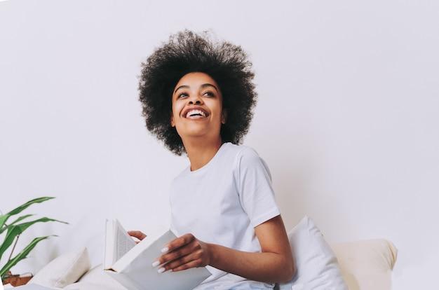 自宅のベッドで休んでいるアフリカ系アメリカ人の女の子-自宅でリラックスした美しい女性