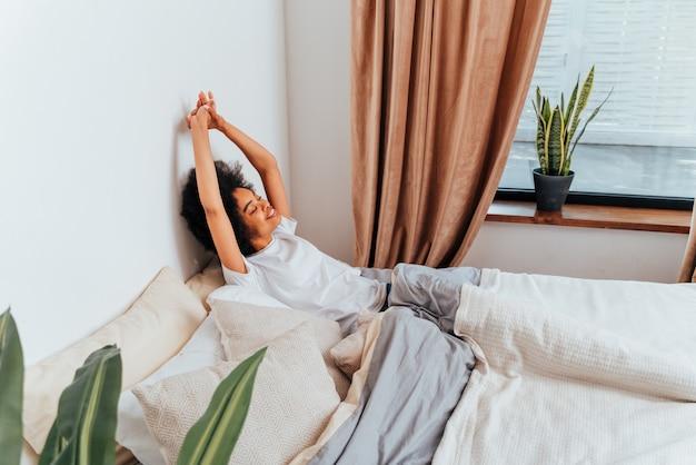 집에서 침대에서 쉬고 있는 아프리카계 미국인 소녀 - 집에서 휴식을 취하는 아름다운 여성
