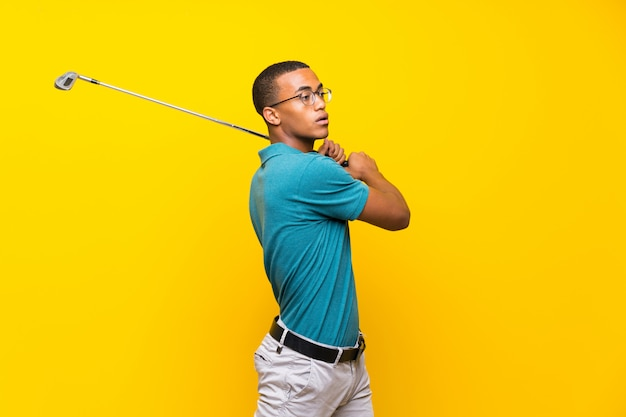 Afro american golfer player man over isolated yellow background