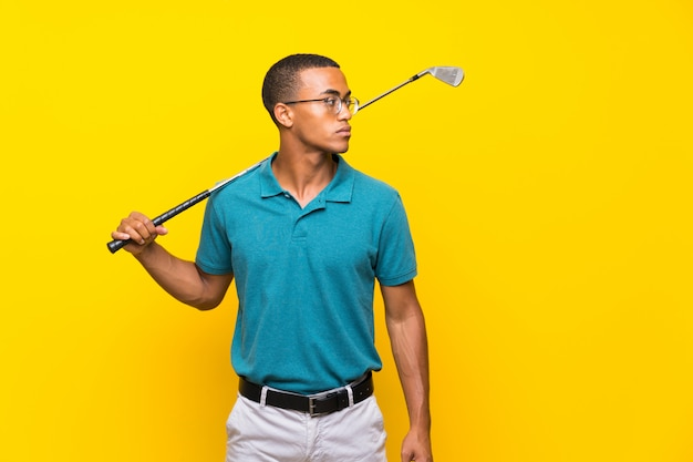 Afro american golfer player man over isolated yellow