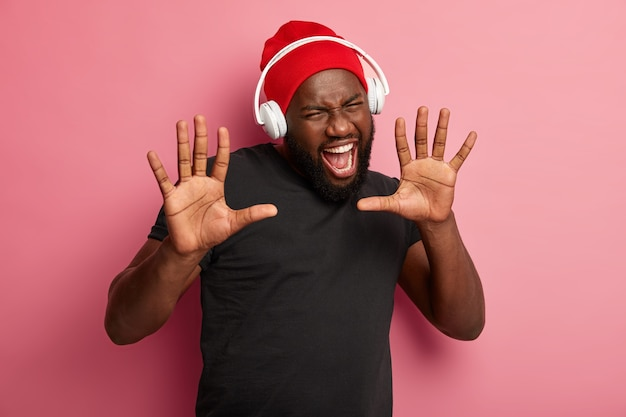 Afro american guy keeps palms forward, opens mouth widely, dressed in red hat and black t shirt, exclaims from joy, enjoys music in headphones