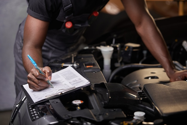 Afro american guy repairing car hood and make notes in notebook