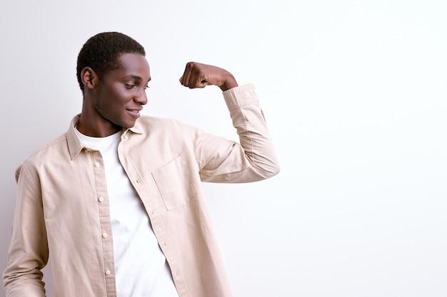 腕の筋肉を示すアフリカ系アメリカ人の男、白いスタジオの背景に分離された強力な強い男