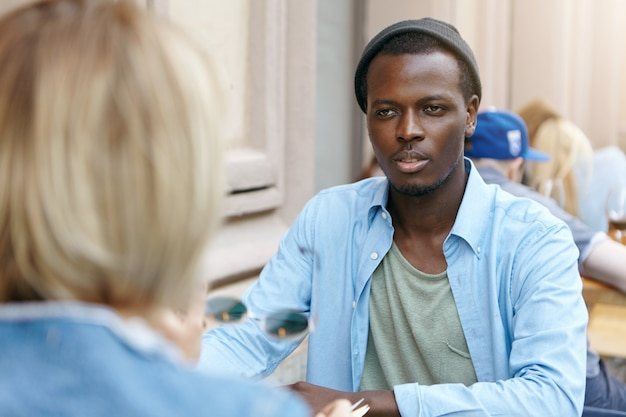 Afro american guy with dark skin dressed in shirt and black hat sitting in front of his female friend, having conversation with each other, discussing news. business partners meeting at cafe
