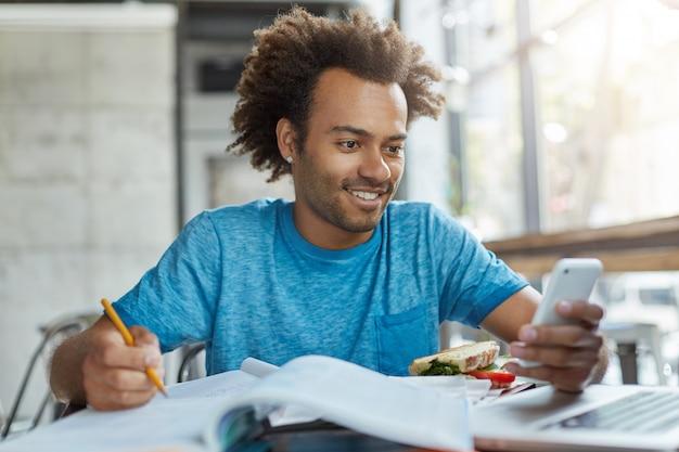 Smsを読みながら電子ガジェットにテキストメッセージを入力して楽しい笑顔で本を書いたり本をコピーしたりする本に囲まれたカフェテリアにいるアフロアメリカンの幸せな学生