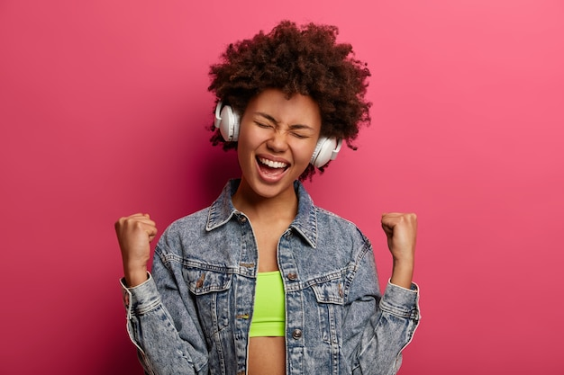 Afro american happy woman clenches fists, feels like winner or champion, enjoys new playlist, listens songs in headphones, wears denim jacket, isolated on pink wall, chills indoor alone