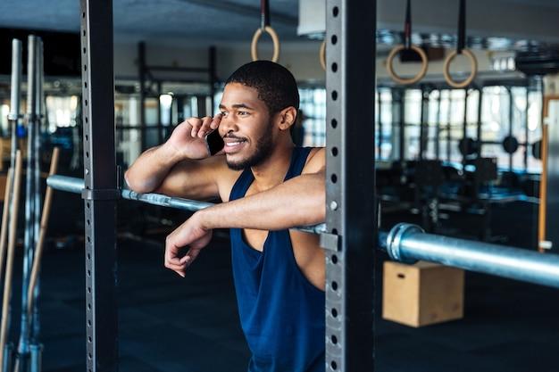 체육관에서 쉬고있는 동안 스마트 폰을 사용하는 아프리카 미국 건강 피트니스 남자