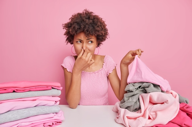 Afro american housewife covers nose as smells dirty laundry squints face from unpleasant stench does domestic chores poses at table folds washed clothes isolated on pink wall. household concept