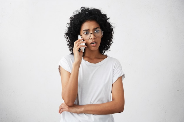 Afro american housewife with curly hair wearing big round glasses and casual t-shirt